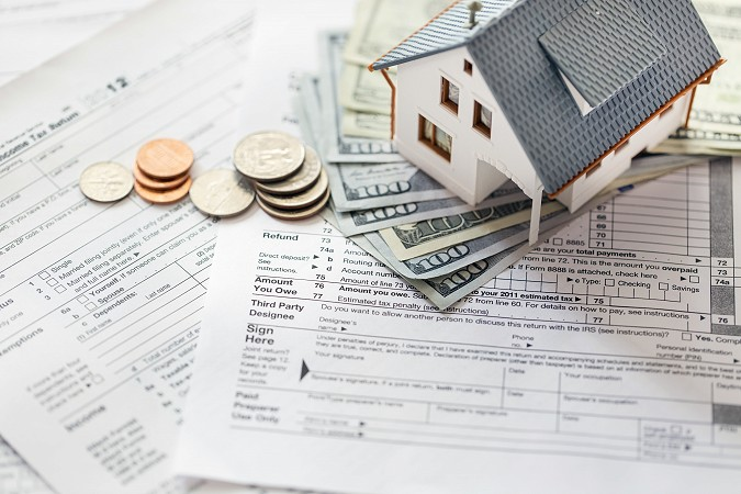 Miniature house with money on tax papers